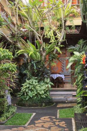 Interior of traditional balinese garden landscaping detail vertical. Patio garden, surrounded by lush natural tropical landscaping motifs, antique stone decor paths and bonsai. Editorial