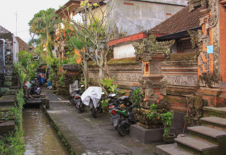 Scooters parked on back alley separating houses, in Ubud, Bali, Indonesia Editorial