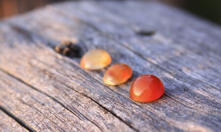 Three colored chalcedony agate gemstones on wooden background shining in the sunlight. Chalcedony gems come in a variety of different colors and are usually polished in round shape.