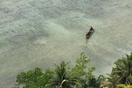 People on boat approaching shore in tropical sea destination island Pasumpahan island, Padang, West Sumatra, Indonesia. Seen from above as the travelers get close to the trees in exotic destination