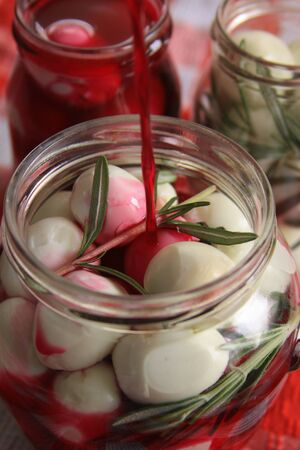 Marinated quail eggs in jars. Preparing quail eggs delicacy for Easter, with beetroot, vinegar, rosemary and pepper
