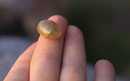 One isolated yellow chalcedony agate gemstone on fingertip shining in the sunlight. Chalcedony gems come in a variety of different colors and are usually polished in round shape. Stock Photo