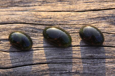 Black jade translucent green stone in sunlight on wood. The black jade is dark green in color, but under the light it is semi-transparent, appreciated by jewelers because the way it shines