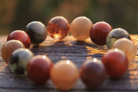 Bracelet jewelry made of different types of round gemstone beads, including translucent red, green, orange, yellow and white. Some of them are rutilated and tourmalinated quartz. Stock Photo