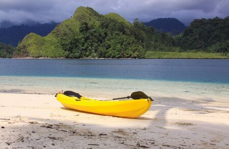 Yellow kayak isolated on sand, on the beach of exotic tropical travel destination Pasumpahan island, Padang, West Sumatra, Indonesia