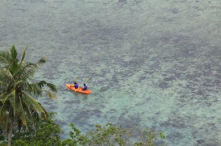 Two people in sea kayak rowing next to island coast tropical sea destination Pasumpahan island, Padang, West Sumatra, Indonesia