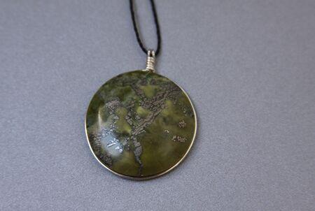 Single peruvian jade stone in handmade jewelry on grey background