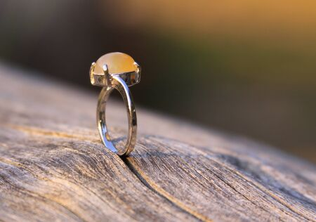 Engagement ring with creamy yellow orange chalcedony agate gemstone on wood. Chalcedony gems come in a variety of different colors and are usually polished in round shape.