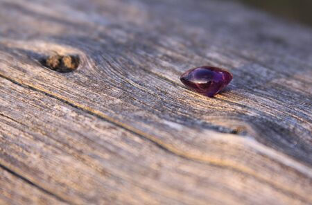 Purple amethyst gemstone on wooden background. The amethyst is violet in color and this stone is cut and polished in round shape