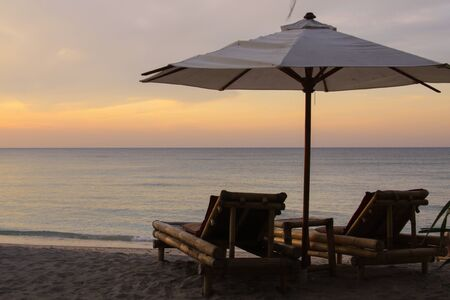 Tropical umbrella and bamboo long chairs on the beach with calm sea at sunset, on Gili Air island, Lombok, Indonesia