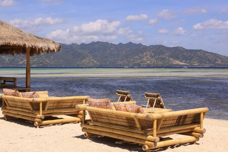 Tropical straw umbrella and sofas with pillows at beach bar on sunny exotic beach overlooking mountains on Gili Air island, Lombok, Indonesia