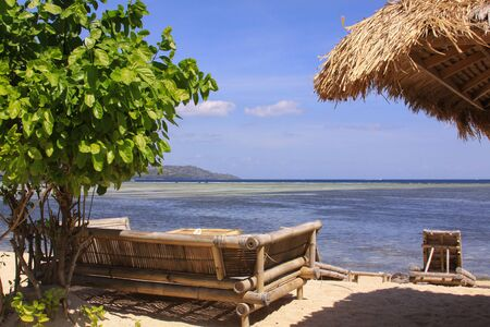 Tropical straw umbrella and sofas with pillows at beach bar on sunny exotic beach overlooking low tide ocean in Gili Air island, Lombok, Indonesia Stockfoto
