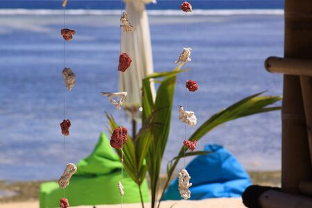 Red and white coral pieces decorations design, hanging on wire at exotic beach bar, with blurred umbrella and sea waves in background, on Gili Air island, Lombok, Indonesia Stockfoto