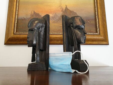 African head sculptures and surgical mask decor. Indoor home isolation time, as social distancing quarantine measures restrict outdoor activity during Coronavirus pandemic lockdown.