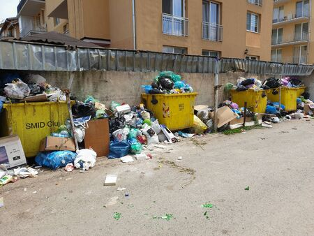 Messy pollution in garbage dump area spills in the streets of Floresti, Cluj, Romania. Trash accumulation in the street from filled containers in apartment buildings neighborhood. Environment problem
