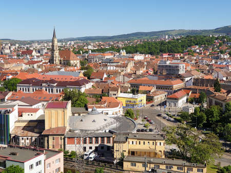 Cluj-Napoca, Romania - May 23, 2020: Cityscape with city center buildings after coronavirus lockdown ease, seen from Belvedere hill, in summer with beautiful blue sky