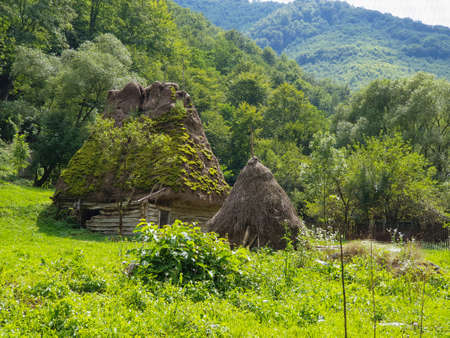 Abandoned traditional old thatched roof wooden house in Apuseni Mountains, Romania. Moss growing on roof, grunge looking house in forest in deserted area in the mountain