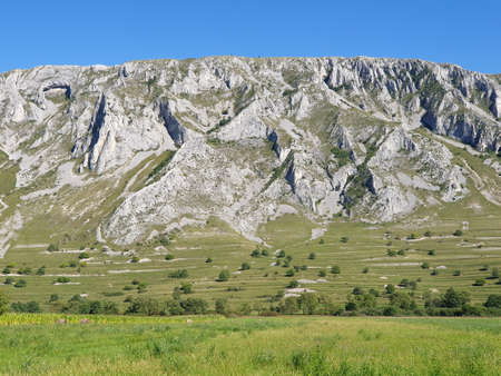 Piatra Secuiului cliffs seen from Coltesti Romania. Piatra Secuiului is a small limestone range in Trascaului mountains, Apuseni, Transylvania, Romania, accessible from Rimetea or Coltesti village