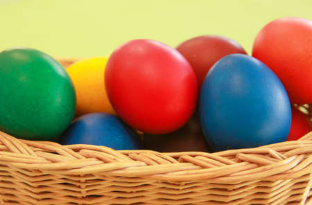Colored painted Easter eggs in wooden basket decoration in preparation for holiday. Painting chicken or duck eggs is a Christian tradition to celebrate Easter all over the world. Stock Photo