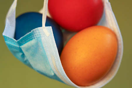 Isolated colored painted Easter eggs in surgical mask, a symbol of coronavirus pandemic. Safety first while celebrating Easter 2020 covid 19 outbreak concept for quarantine holiday in self isolation.