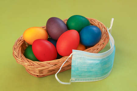 Isolated colored painted Easter eggs in wooden basket decoration with surgical mask, a symbol of coronavirus pandemic. Easter 2020 covid 19 outbreak concept for quarantine holiday