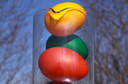 Colored painted Easter eggs in glass vase or carafe in preparation for holiday. Painting chicken or duck eggs is a Christian tradition to celebrate Easter all over the world.