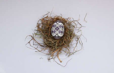 Isolated traditional handmade Easter eggs vintage decoration on hay. Seasonal motif on hand wax painting technique from Bucovina, Romania used to decorate Easter eggs in Moldova and Eastern Europe.
