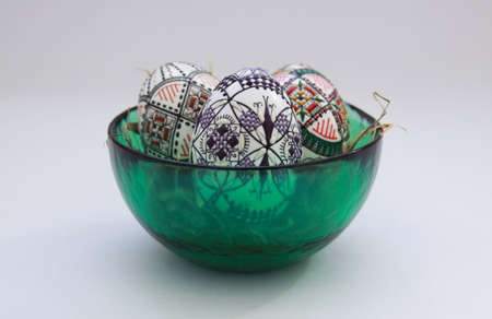 Isolated traditional handmade Easter eggs in glass bowl on hay. Hand wax painting technique from Bucovina, Romania used to decorate Easter eggs in Moldova and Eastern Europe