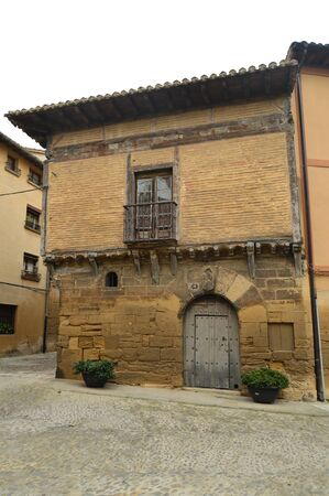 Medieval Style Facade With A Beautiful Door With Background The Church Of The Assumption In Briones. Architecture, Art, History, Travel. December 27, 2015. Briones, La Rioja, Spain.