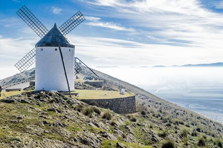 Set of windmills on top of Cerro Calderico with thick fog in the valley in Consuegra. December 26, 2018. Consuegra Toledo Castilla La Mancha Spain Europe. Travel Tourism Street Photography.