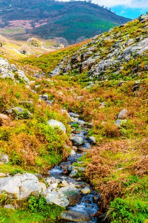 Beautiful stream that descends on the slopes of the Sierra de Gredos that comes from the Almanzor Peak. Stock Photo
