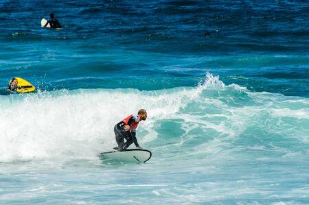 Redhead Man With Beard Breaking Waves On Las Americas Beach. April 11, 2019. Santa Cruz De Tenerife Spain Africa. Travel Tourism Street Photography. Stock Photo