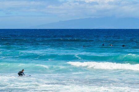 Long Haired Brunette Woman Entering The Atlantic Ocean To Surf Waves On Las Americas Beach. April 11, 2019. Santa Cruz De Tenerife Spain Africa. Travel Tourism Street Photography. Imagens