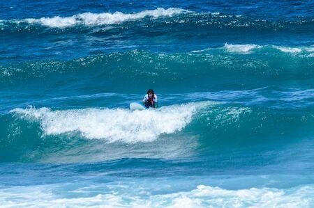 Long Haired Brunette Woman Catching Waves On Las Americas Beach. April 11, 2019. Santa Cruz De Tenerife Spain Africa. Travel Tourism Street Photography. Stock Photo