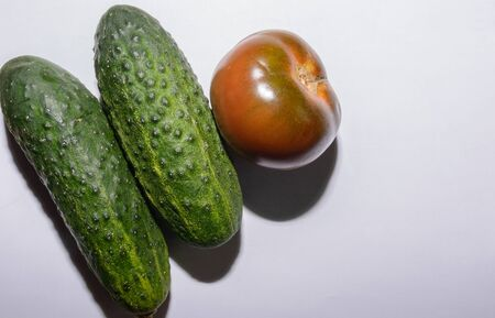 Aerial Shot Of A Group Of Two Fresh Green Cucumbers And A Kumato Tomato On White Background