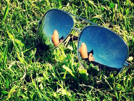 Sunglasses on grass reflecting a young man lying on grass