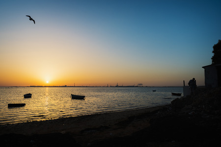 View of a sunset at one beach of San Fernando, Cadiz, Spain, with some fisherman Фото со стока