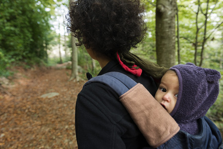 confortable: mother carrying her baby do trekking through the woods