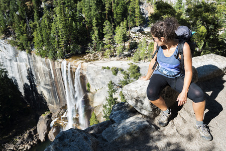 admires: Photo of a hiker resting at the top of a cliff while she admires the landscape and the waterfall