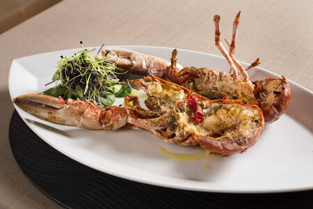 lobster boat: White plate with boat form with a lobster with vegatables