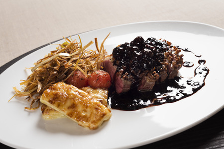 chese: White plate with a piece of meat with sauce, grilled cherry tomatoes and fried chese