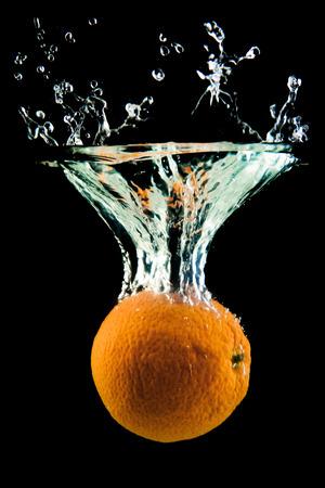 frescura: naranja sobre fondo negro que cae y salpicaduras de agua, dando una sensación única de frescura y vitalidad Foto de archivo
