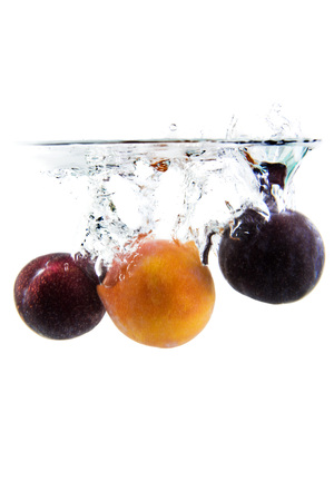 clear water: plum on white background falling and splashing water, giving a unique feeling of freshness and vitality