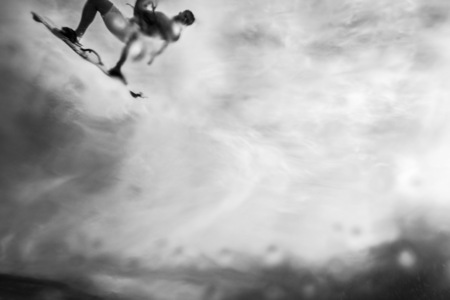 passing over: a black and white abstract image of a surfer flying through the sky passing over the camera
