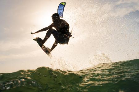 Hintergrundbeleuchtung eines Surfers, der über das Ozeanwasser vor dem Sonnenuntergang springt Standard-Bild