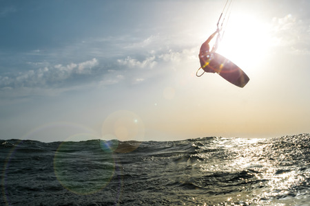 Surfer jumping in front of the sun at sunset over the golden sea, while a beautiful flare enters the camera