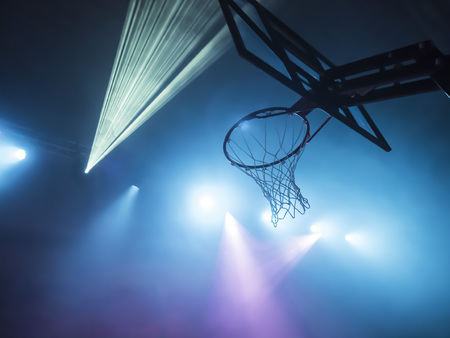 Spectacular image of a basketball basket with the stadium lit with disco lights and smoke