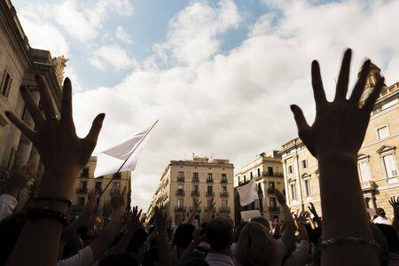 mains au premier plan et rétro-éclairé les gens manifestant massivement avec des drapeaux et des bannières blanches dans les rues d'une ville européenne Banque d'images
