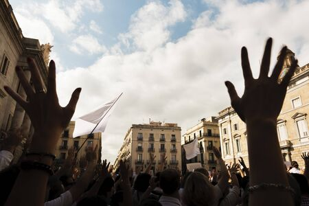 hands in the foreground and back lit people demonstrating massively with flags and white banners through the streets of a European city Banque d'images