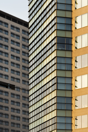 Vertical composition with a close-up of facades of concrete buildings, which have dull colors, to use as background.